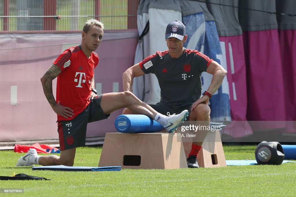 Rafinha (L) of FC Bayern Muenchen practices with fitness coach Peter Schloesser during a training session at the club's Saebener Strasse training ground on July 12, 2018 in Munich, Germany.