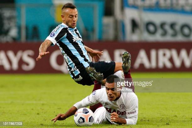 Rafinha of Gremio competes for the ball with José Sand of Lanus during a match between Gremio and Lanus as part of group H of Copa CONMEBOL...
