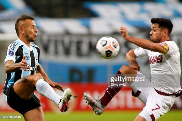 Rafinha of Gremio competes for the ball with Lautaro Acosta of Lanus during a match between Gremio and Lanus as part of group H of Copa CONMEBOL...