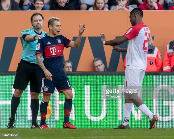 Rafinha of Muenchen and Sergio Duvan Cordova Lezama of Augsburg argue during the Bundesliga match between FC Augsburg and FC Bayern Muenchen at...