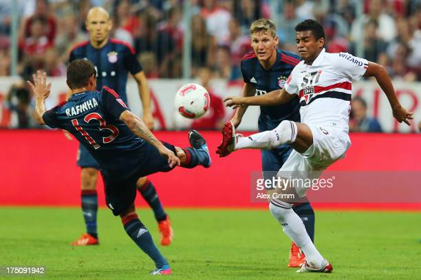Rafinha of Muenchen is challenged by Reinaldo of Sao Paulo during the Audi Cup match between FC Bayern Muenchen and FC Sao Paulo at Allianz Arena on...