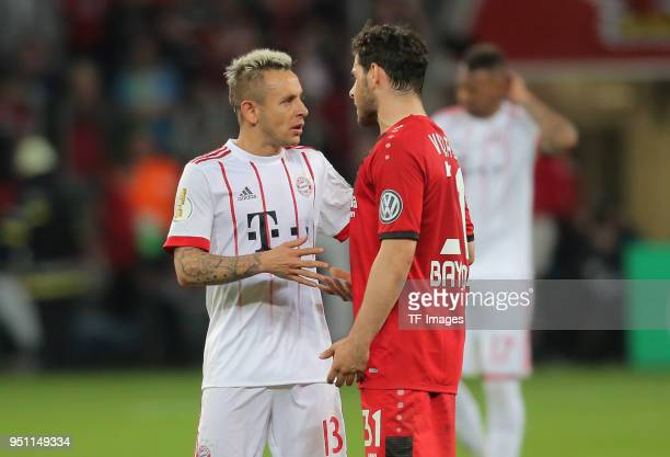 Rafinha of Muenchen speaks with Kevin Volland of Leverkusen during the DFB Cup semi final match between Bayer 04 Leverkusen and Bayern Munchen at...
