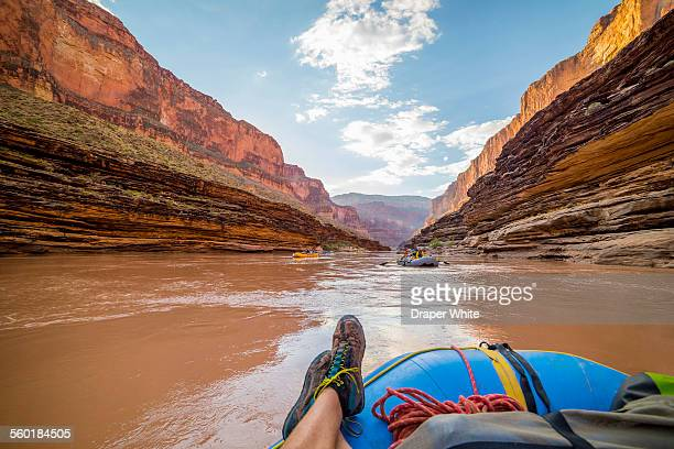 Rafter floats down river with feet up.