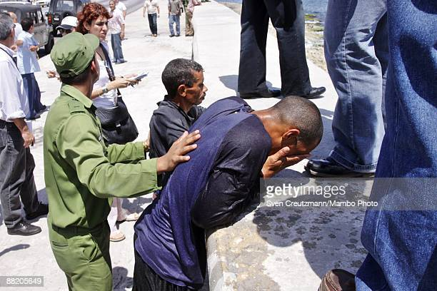 A rafter is detained by Cuban security officers after seven men failed in an attempt to leave the island at the Malecon waterfront on June 4 2009 in...