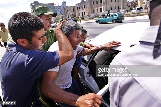 A rafter is put into a car by Cuban security officers after seven men failed in an attempt to leave the island at the Malecon waterfront on June 4...