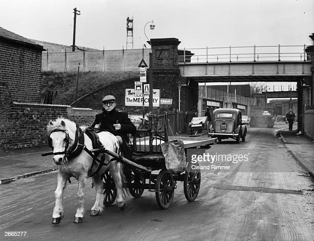 Rag and bone man Frank Gironella with his pony Titch who pulls an empty cart along a road near the Millwall canal London