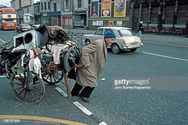 A rag and bone man pulling a handcart loaded with waste and scrap along a street in Manchester England in 1976