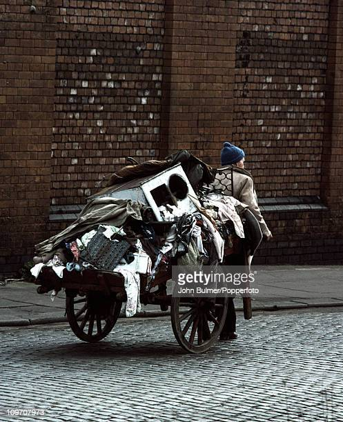 A rag and bone man pulling a handcart loaded with waste rags and scrap in Manchester England in 1976
