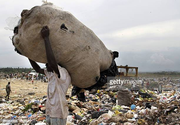 A rag picker carries a bag containing plastic items at the Duquesa dump in Santo Domingo on April 21 2010 It is estimated that some 1500 scavengers...