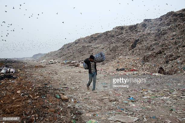 A rag picker carries a mattress at the Ghazipur landfill site in the east of New Delhi India on Friday May 30 2014 New Delhi whose population will...