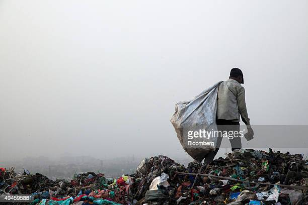 A rag picker carries a sack of sorted recyclable materials collected from garbage at the Ghazipur landfill site in the east of New Delhi India on...