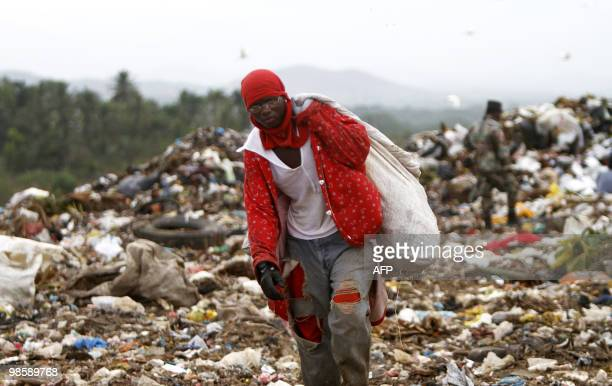 A rag picker carries a sack with plastic items collected at the Duquesa dump in Santo Domingo on April 21 2010 It is estimated that some 1500...