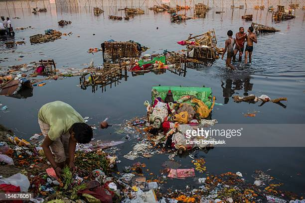 A rag picker sorts through refuse left over from Hindu devotees immersing an idols of Goddess Durga into the Yamuna river on the last day of the...