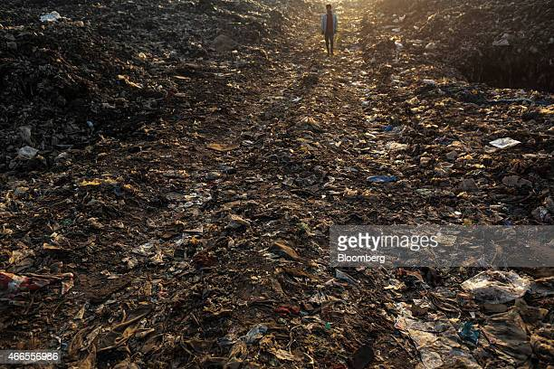 A rag picker walks though garbage at the Deonar landfill site in Mumbai India on Wednesday March 11 2015 Mumbai is running out of space for its waste...