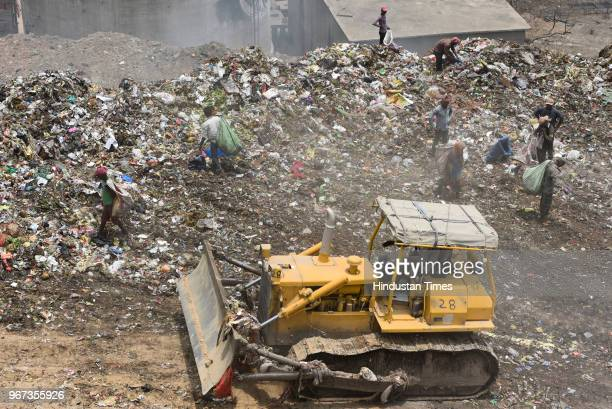 Rag pickers collect usable items from a mountain formed by garbage at a landfill site ahead of the World Environment Day, at Okhla on June 4, 2018 in...
