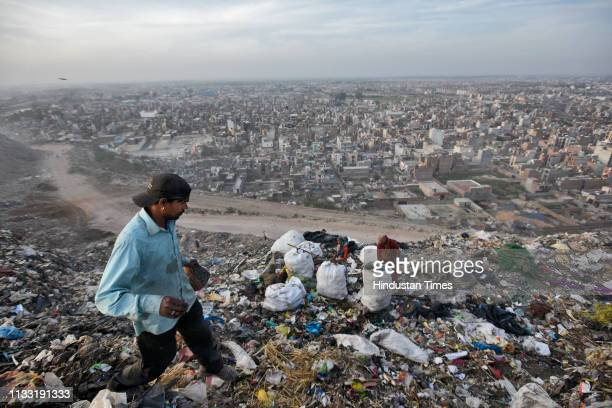 Rag pickers collect usable items from a pile of waste at Bhalswa Landfill site on March 27 2019 in New Delhi India