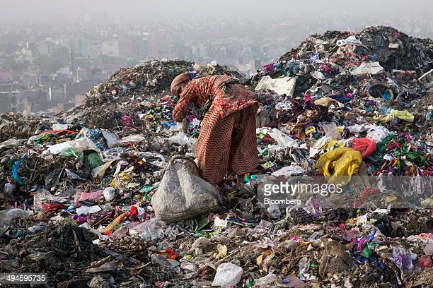 A rag pickers sorts through garbage picking out recyclable materials to sell at the Ghazipur landfill site in the east of New Delhi India on Friday...