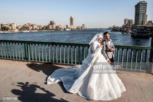 Ragab Uwais poses for a picture with his bride before a video cameraman for their wedding video along al-Gamaa bridge connecting the Egyptian capital...