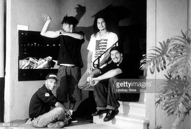 Rage Against the Machine vocalist Zack de la Rocha raises his arm to play with his shadow amusing guitarist Tom Morello drummer Brad Wilk and bassist...