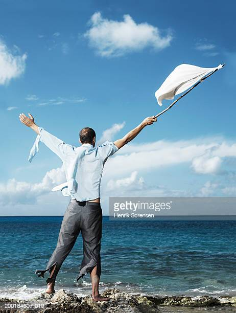 Ragged businessman on beach, waving improvised flag, rear view