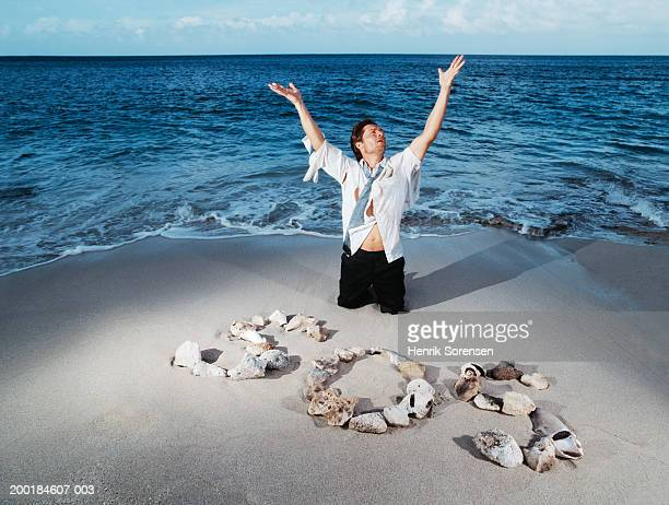 ragged businessman on beach with 's.o.s.' made from rocks and shells - sos einzelwort stock-fotos und bilder