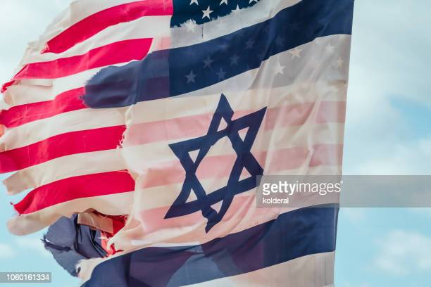 Ragged National flags of Israel and USA waving