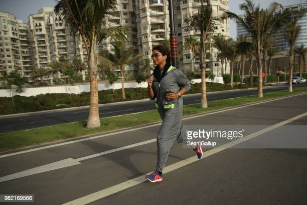 Raghda Safdar a university administrator and a divorced mother of three, runs wearing an abaya designed specifically for sports on a bicycle road...