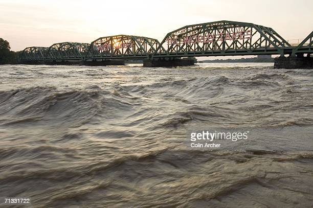 Raging flood waters flow below the famous Trenton Makes Bridge which crosses the Delaware River between Trenton and Pennslyvania on June 28 in...