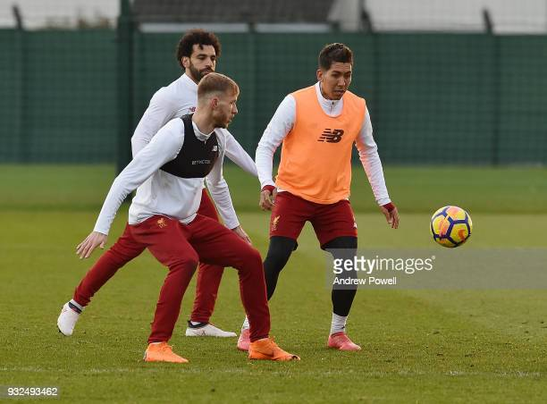 Ragnar Klavan and Roberto Firmino of Liverpool during the training session at Melwood Training Ground on March 15 2018 in Liverpool England