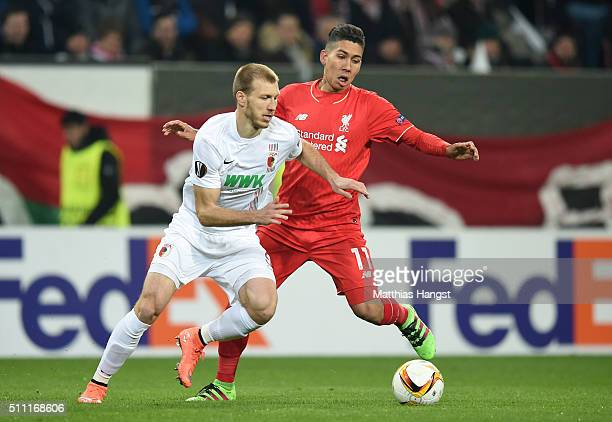 Ragnar Klavan of Augsburg and Roberto Firmino of Liverpool compete for the ball during the UEFA Europa League round of 32 first leg match between FC...