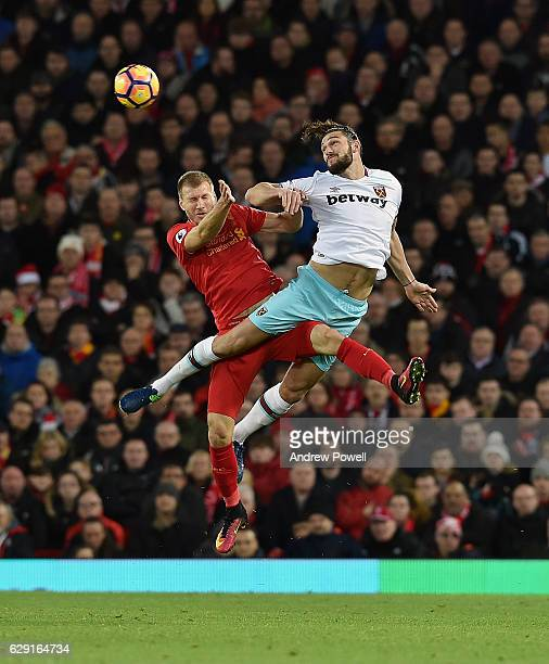 Ragnar Klavan of Liverpool goes up with Andy Carroll of West Ham United during the Premier League match between Liverpool and West Ham United at...