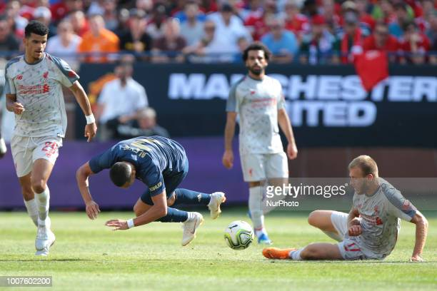 Ragnar Klavan of Liverpool lands on the field as Alexi Sanchez of Manchester United falls after losing control of the ball during an International...