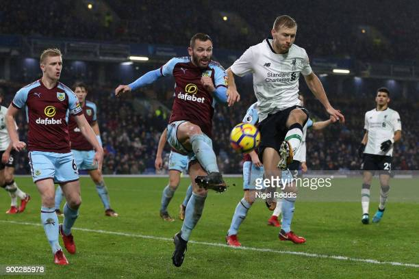 Ragnar Klavan of Liverpool shoots while under pressure from Phil Bardsley of Burnley during the Premier League match between Burnley and Liverpool at...
