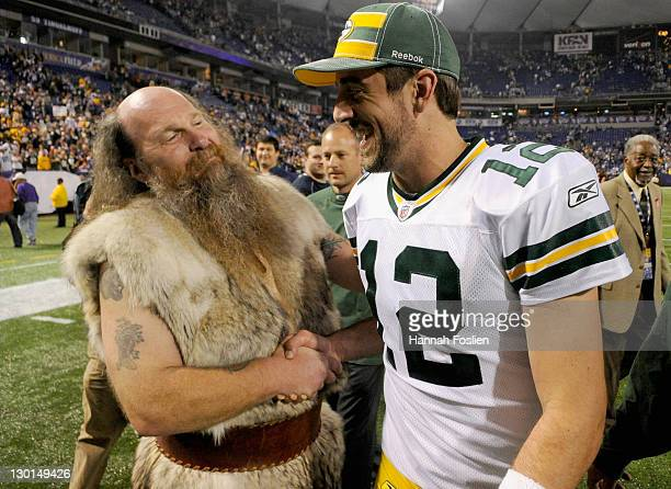 Ragnar mascot for the Minnesota Vikings shakes hands with Aaron Rodgers of the Green Bay Packers after the Packers defeated the Vikings on October 23...