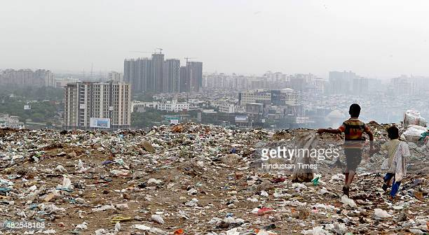 Ragpicker children pass over the hillock of garbage at the Gazipur Landfill with Skyline of Noida city in back ground on July 31 2015 in New Delhi...