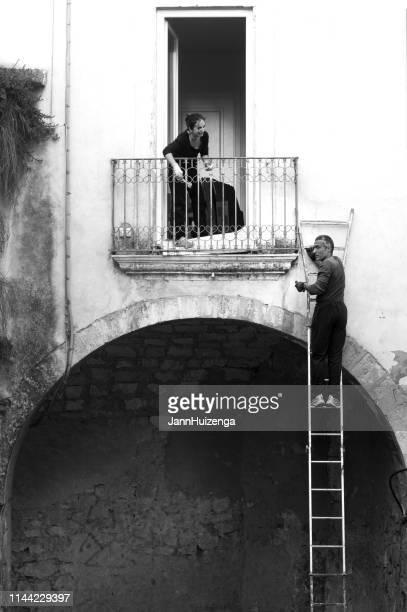 ragusa, sicilia, italia: hombre en escalera, mujer en el balcón - sicilia fotografías e imágenes de stock