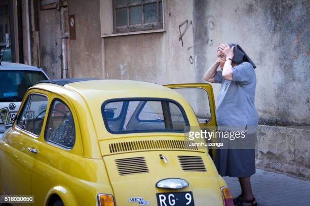 Ragusa, Sicily: Nun Adjusts Veil Near Yellow Vintage Fiat 500