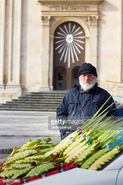ragusa, sicily: senior vendor sells woven palm fronds - palm sunday photos stock pictures, royalty-free photos & images