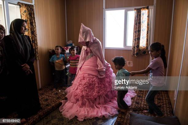Rahaf Yousef a Syrian refugee from Daraa poses for a portrait in her family's trailer as she is surrounded by female relatives on the day of her...