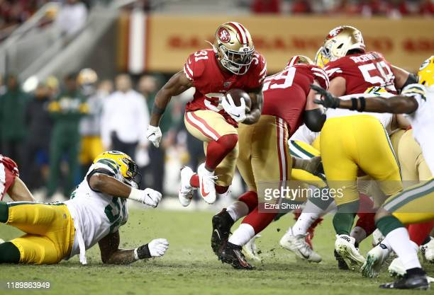 Raheem Mostert of the San Francisco 49ers breaks through the line in route to running in for a touchdown against the Green Bay Packers at Levi's...