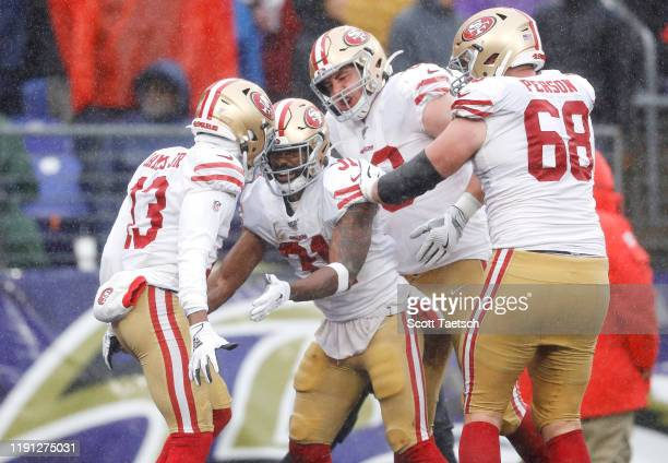 Raheem Mostert of the San Francisco 49ers celebrates with teammates after rushing for a 40-yard touchdown during the second quarter against the...