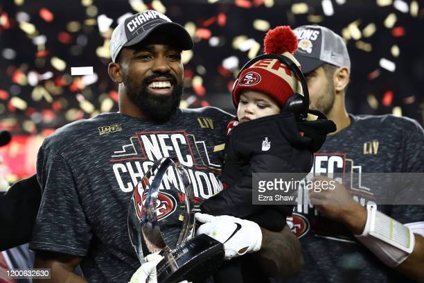 Raheem Mostert of the San Francisco 49ers celebrates with the George Halas Trophy while holding his son Gunnar after winning the NFC Championship...