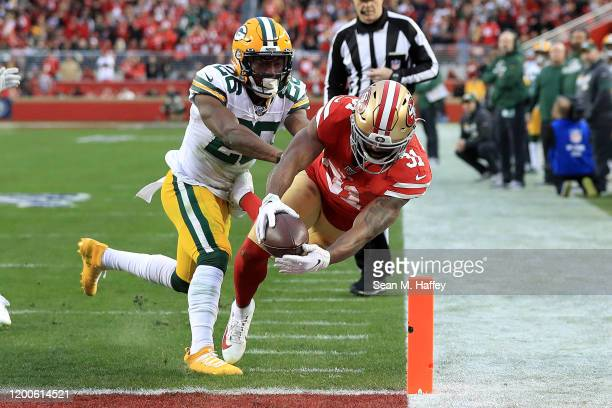 Raheem Mostert of the San Francisco 49ers dives into the end zone for a touchdown against Darnell Savage of the Green Bay Packers in the first half...
