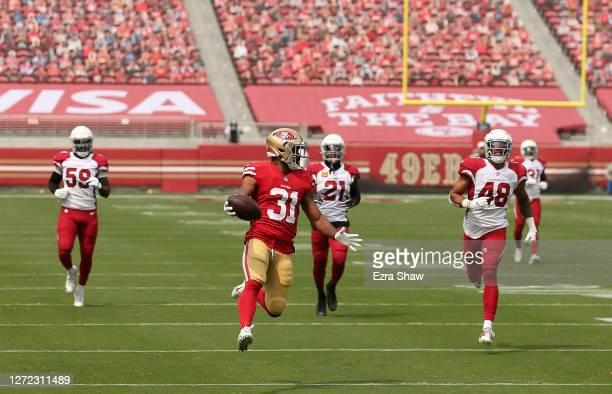 Raheem Mostert of the San Francisco 49ers gets past Jordan Hicks, Patrick Peterson, and Isaiah Simmons of the Arizona Cardinals on his way to a...