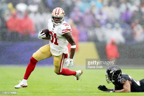 Raheem Mostert of the San Francisco 49ers rushes for a 40-yard touchdown during the second quarter as Marcus Peters of the Baltimore Ravens is unable...