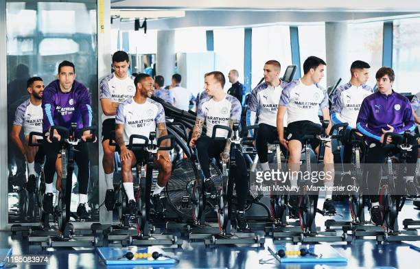 Raheem Sterling and Angelino of Manchester City warm up in the gym prior to the training session at Manchester City Football Academy on December 20...