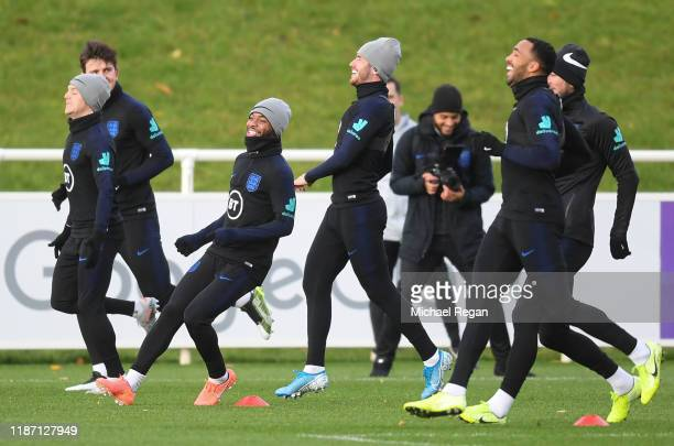 Raheem Sterling and Ben Chilwell laugh during the training session at St Georges Park on November 12 2019 in BurtonuponTrent England