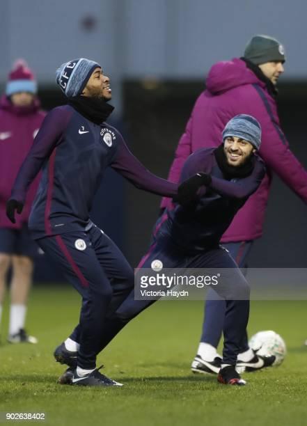 Raheem Sterling and Bernardo Silva joke during training at Manchester City Football Academy on January 8 2018 in Manchester England