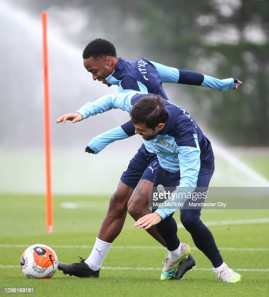 Raheem Sterling and Bernardo Silva of Manchester City in action during a training session at Manchester City Football Academy on July 14 2020 in...