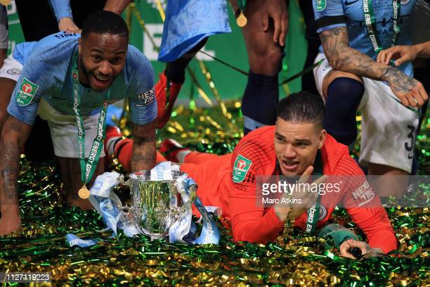 Raheem Sterling and Ederson of Manchester City pose with the trophy during the Carabao Cup Final between Chelsea and Manchester City at Wembley...